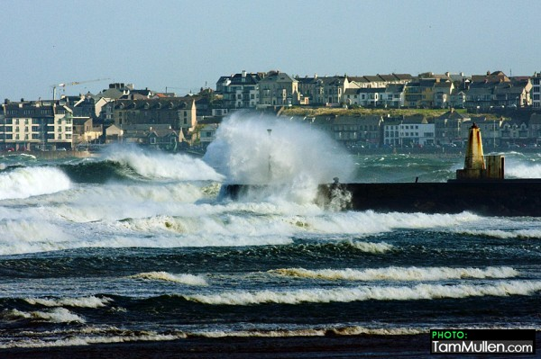 Waves crash into castlerock during the large swell